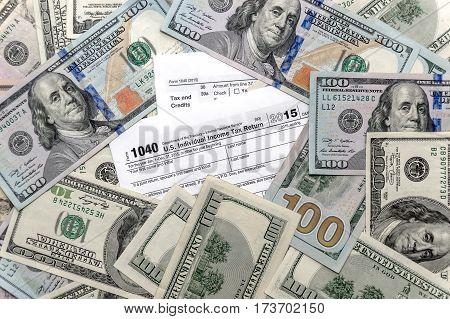 Tax form 1040 with US dollar bills.