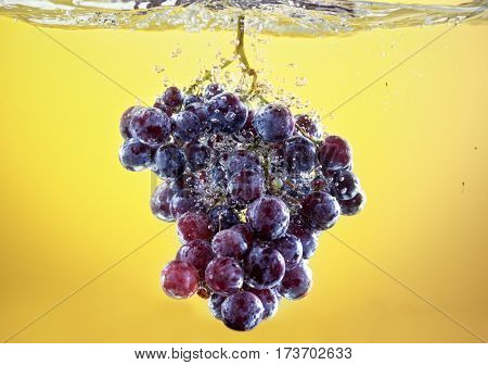 grapes drop in tank filled with water background