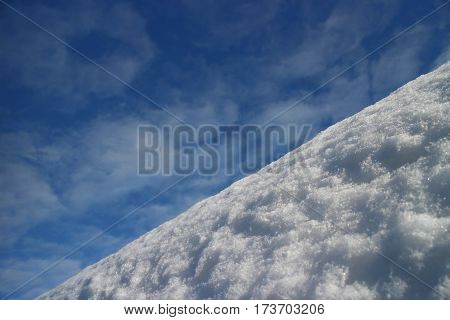 Steep descent mountain covered with snow against the blue sky low angle view