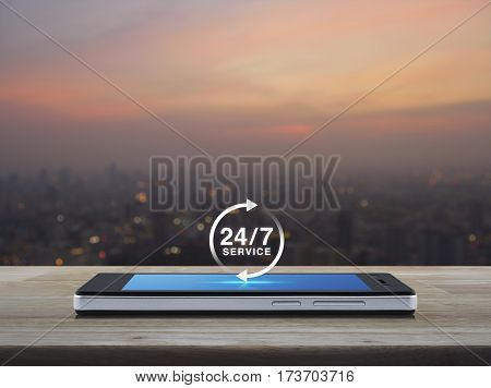 24 hours service icon on modern smart phone screen on wooden table over blur of cityscape on warm light sundown Full time service concept