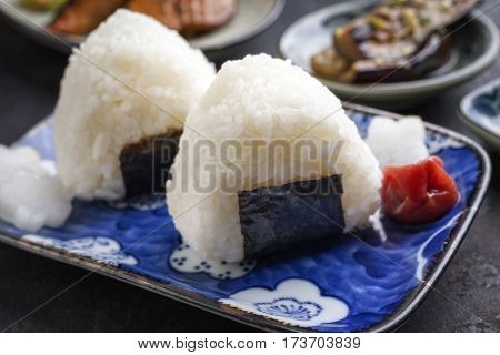 Traditional Japanese Onigiri with Umeboshi as garnish on a bowl