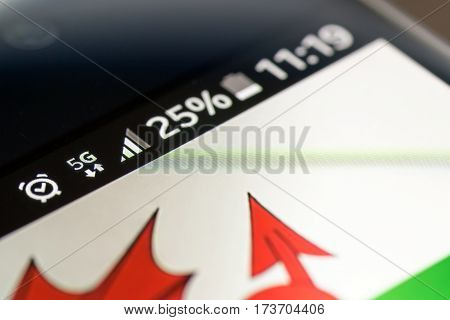Smartphone on wooden background with 5G network sign 25 per cent charge and Wales flag on the screen.