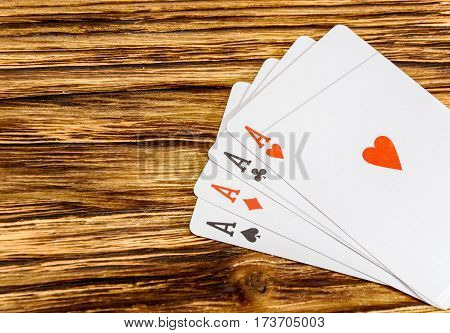Four aces on a wooden background .