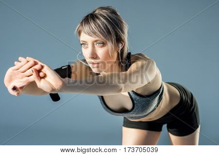 woman in sportive clothes with earphones stretching on grey poster