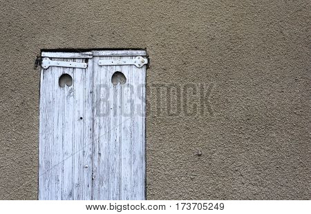 Window with old wooden shutters with peeling white paint and wrought iron hinges. background - yellow pink walls. France. Lyon.