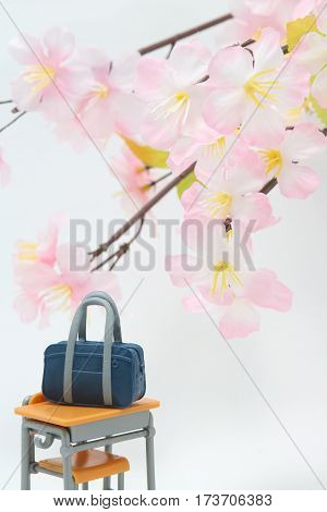 Satchel and cherry blossoms on white background.  Entrance ceremony concept.
