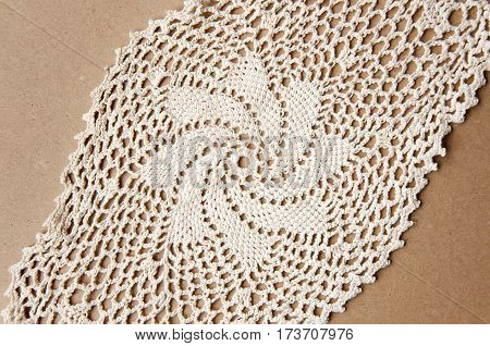 Knitted homemade white lace doily with a star pattern on cardboard.