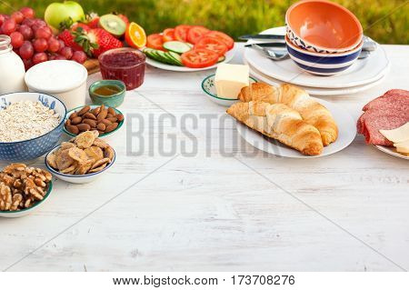Healthy continental breakfast served in the garden ham cheese cereals nuts jam vegetables croissants selective focus copy space for text