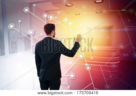 Rear view of businessman pretending to touch invisible screen against modern room overlooking city