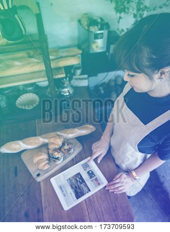 Young patissier woman learning new recipe on digital tablet