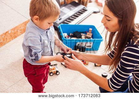 Caregiver helps the child to repair the toy car in kindergarten. Focus on the hands