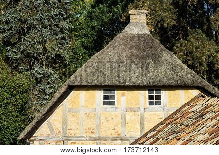European building styles. detail of yellow timber framed house with white small windows and thatched roof
