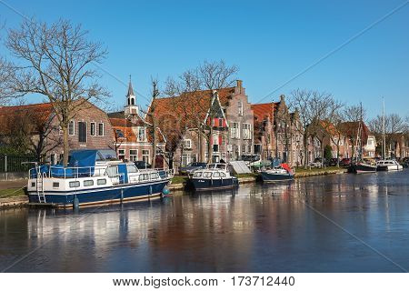 EDAM, NORTH HOLLAND/ THE NETHERLAND - JANUARY 16, 2017:  Houses along the frozen canal on one of the central streets in winter