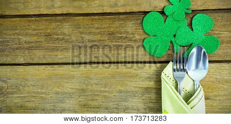 St Patricks Day fork and spoon wrapped in napkin with shamrocks on wooden table