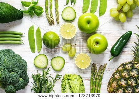 Health concept: top view of green fruits and vegetables: apples pears salad broccoli cucumber asparagus beans manetouts kiwi grapes avocado mango lime on the with wooden table
