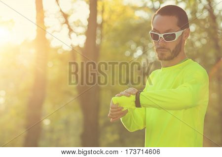 Jogger making a pause in the park and checking his running time.