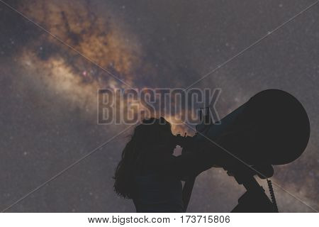 Girl looking at the stars through a telescope. Stars are naturally de-focused.