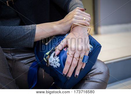 woman hands with fau bijou on blue back pack