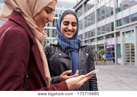 British Muslim Women Texting On Mobile Phone Outside Office