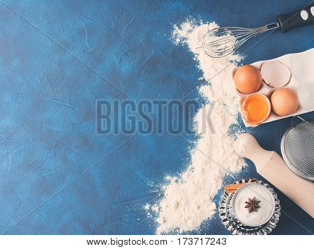 Baking tools rolling pin whisk and ingredients flour egg, sugar on dark blue background. top view flat lay. Making dough for cookies cake pie process concept