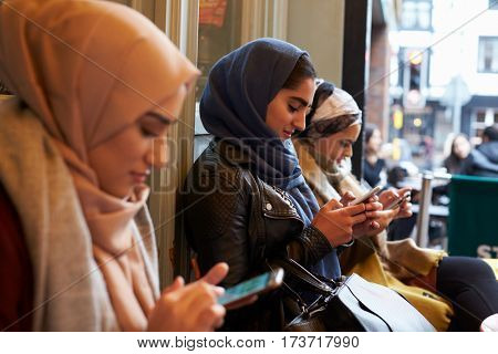 Group Of British Muslim Women Texting Outside Coffee Shop