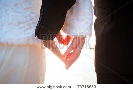 bride and groom hands making heart together