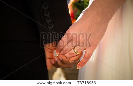 bride and groom hands during wedding ceremony