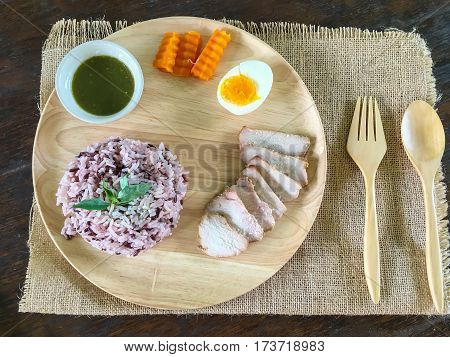 Barbecue and red pork with gravy sauce and brown rice on wood plate