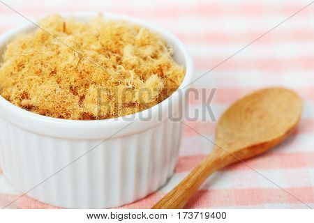 dried pork floss in white cup with wooden spoon on napery background.