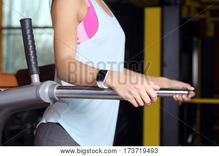 Young woman with fitness tracker training in gym