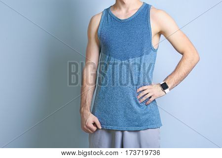 Young man with fitness tracker on color background