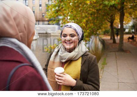 British Muslim Female Friends Talking By River In City