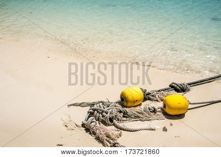 old rope with yellow floating wood recue on sand for background