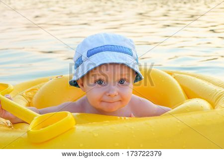 Happy baby in a yellow inflatable raft on the open water surface. Portrait small child in yellow rubber ring.