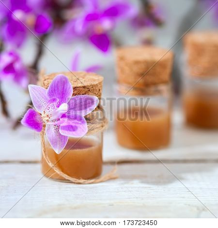 Spa Setting With Cosmetic Cream, Gel And Purple Orchid On White Wooden Table Background.