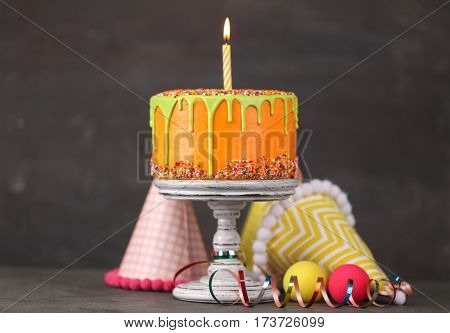 Delicious cake with happy birthday candle on dark background