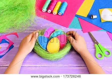 Small child made Easter decoration. Child holds beautiful felt Easter eggs and sisal nest decoration in his hands. Craft tools and materials on a table. Easy handmade Easter gift idea for kids