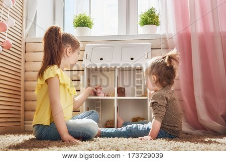 Happy sisters girls play with doll house at home. Funny lovely children are having fun in kids room.