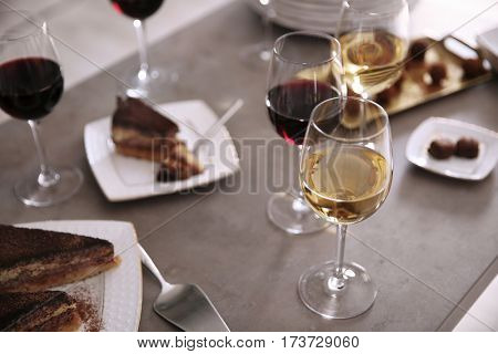 Delicious chocolate desserts and wine on grey table