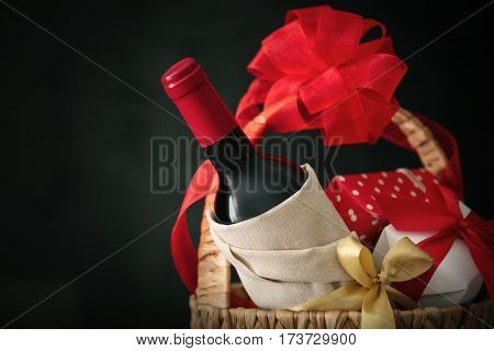 Wine bottle with gift boxes in wicker basket on dark background