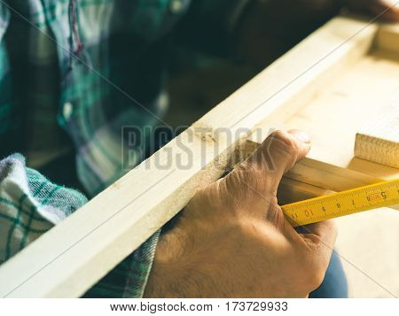 Man crafting wooden chair object keeping wooden boards in hands. Measuring with meter tool. Do it yourself project making process