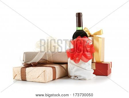 Decorated wine bottle and gift boxes on white background