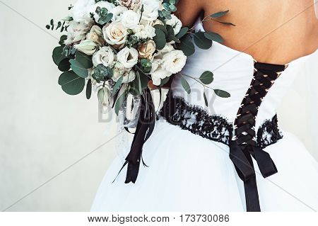 bride in a luxurious wedding dress with a black lace holding a wedding bouquet decorated with a black ribbon made of roses