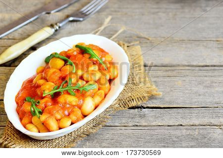 Homemade beans stew on a plate and on vintage wooden background with copy space for text. White beans stew with carrots, tomato sauce and fresh arugula. Tasty and healthy beans side dish. Rustic style