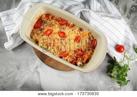 Delicious stuffed cannelloni in baking dish on wooden board