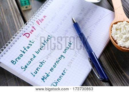 Spoon with curd and notebook on wooden table. Milk diet concept