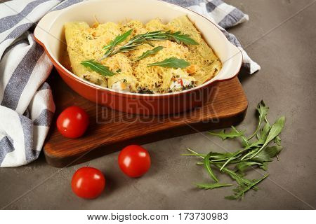 Delicious stuffed cannelloni in baking dish on table