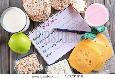 Diary and different dairy products on wooden background