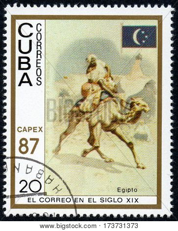 UKRAINE - CIRCA 2017: A stamp printed in Cuba shows a man with a cargo moved on a camel Egypt the series The mail in the nineteenth century circa 1987
