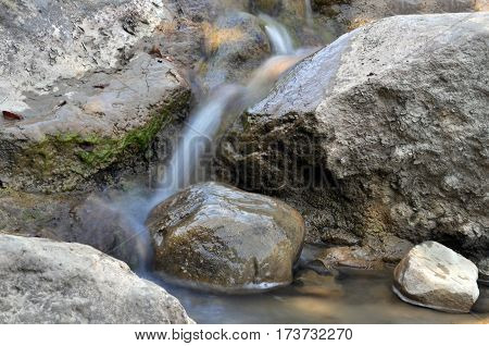 Arpat stream in the mountains of the Crimean peninsula. Moving blurred water on the stones.